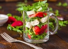 新鲜蔬菜在玻璃瓶子的草莓沙拉在自然土气 免版税图库摄影