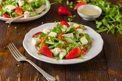 新鲜蔬菜在白色板材的草莓沙拉在自然土气书桌上 库存图片