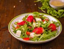新鲜蔬菜在白色板材的草莓沙拉在自然rusti 图库摄影