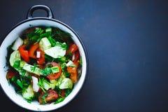 新鲜蔬菜夏天沙拉在一块板材的在黑背景,蕃茄,黄瓜,莳萝,荷兰芹,葱 关闭,顶视图 库存图片