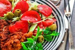 新鲜蔬菜春天沙拉用蕃茄、绿橄榄和荷兰芹在白色碗在木桌上 库存照片