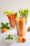 新鲜蔬菜棍子用酸奶在白色背景浸洗 库存图片