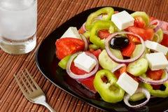 新鲜蔬菜沙拉和一块玻璃与ouzo 库存照片