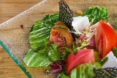 新鲜蔬菜沙拉用新鲜的蕃茄、莴苣和芝麻菜 新鲜的沙拉顶视图在玻璃板的在木桌上 库存图片