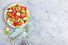 新鲜蔬菜沙拉用蕃茄、黄瓜、甜椒和芝麻籽 在白色板材的菜沙拉 免版税库存图片