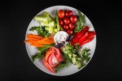 新鲜蔬菜的分类在板材的 在黑暗的背景,顶视图 免版税库存照片