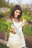 给新鲜蔬菜的愉快的逗人喜爱的妇女 免版税库存照片
