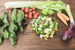 新鲜蔬菜的混合在准备好一张老的桌上的被烹调 图库摄影