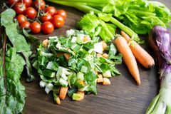 新鲜蔬菜的混合在准备好一张老的桌上的被烹调 库存图片