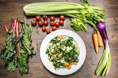 新鲜蔬菜的混合在准备好一张老的桌上的被烹调 免版税图库摄影