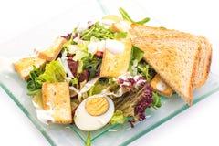 新鲜蔬菜芝麻菜沙拉用乳酪、鸡蛋和面包切片在白色背景隔绝的玻璃板,产品摄影 免版税库存图片