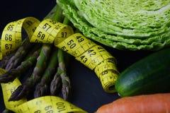 新鲜蔬菜:圆白菜、鲕梨、黄瓜、芦笋、红萝卜和测量的米 库存照片