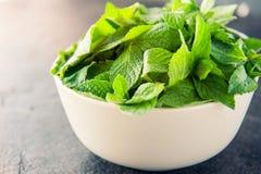 新鲜薄荷在陶瓷碗离开在黑暗的石背景 健康素食食物概念 选择聚焦 复制空间f 免版税库存图片