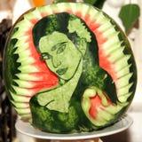 新鲜雕刻女孩从一个裁减西瓜的` s面孔 图库摄影