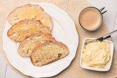 新鲜面包、自创黄油和咖啡在木背景 免版税图库摄影