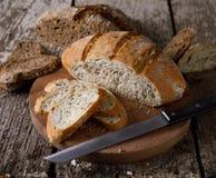 新鲜面包切片和切刀在土气桌上 免版税库存照片
