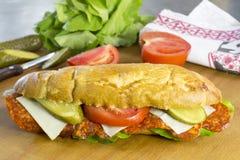 新鲜面包卷充满意大利辣味香肠、乳酪、黄瓜、蕃茄和莴苣 库存图片