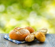 新鲜面包和方格的餐巾在木桌上  库存照片