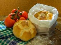新鲜面包和蕃茄在桌上 免版税图库摄影