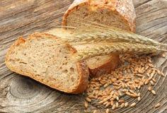 新鲜面包和麦子在木背景 库存图片