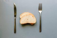 新鲜面包在叉子和刀子之间的灰色桌上说谎 库存图片