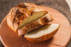 新鲜面包明亮的大面包与一个发光的外壳的在一个圆的厨房板 免版税图库摄影