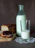 新鲜面包用果酱、瓶和一杯牛奶 库存图片