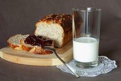 新鲜面包用果酱和一杯牛奶 库存照片