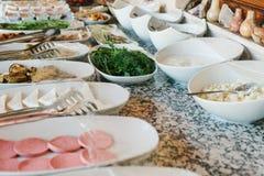 新鲜食品品种在桌上的 表用食物:白色板材和碗用香肠切了乳酪并且烘烤了 免版税库存图片