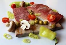 新鲜食品-有切片的木切板蒜味咸腊肠和火腿、橄榄、蘑菇和被切的蕃茄和青椒 库存照片