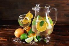 新鲜,健康汁液用桔子,石灰,在土气背景的薄菏 一份素食饮料的自然果子成份 免版税图库摄影