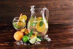 新鲜,健康汁液用桔子,石灰,在土气背景的薄菏 一份素食饮料的自然果子成份 免版税库存照片