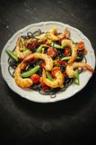 新鲜,可口黑意粉用烤虾,蕃茄,辣椒,在一块白色板材 库存照片