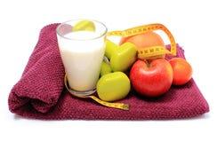 新鲜水果、卷尺、牛奶和哑铃在紫色毛巾 库存照片
