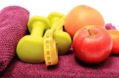 新鲜水果、卷尺和绿色哑铃在紫色毛巾 免版税库存图片
