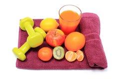 新鲜水果、在紫色毛巾的杯汁液和哑铃 免版税库存照片