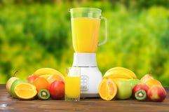 新鲜水果和杯在土气木桌上的汁液 免版税库存照片