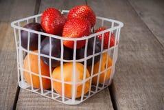 新鲜水果和草莓在小塑料篮子 免版税图库摄影