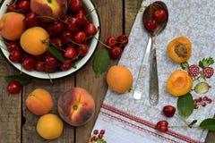 新鲜水果和莓果在木背景 成熟甜樱桃和杏子在碗在厨房用桌上 库存图片