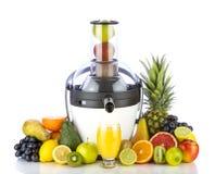 新鲜水果和玻璃用汁液在榨汁器附近 库存图片
