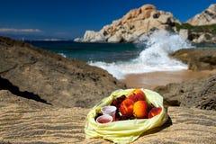 新鲜水果桃子和樱桃在塑料后面在海滨,背包徒步旅行者吃午餐,新鲜水果在岩石在海滩 免版税库存图片