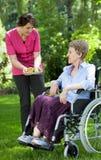 给新鲜水果的护士年长妇女 免版税库存照片