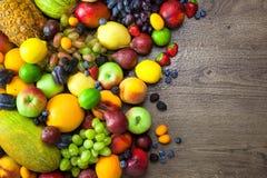 新鲜水果的混合用水在黑暗的木桌上下降 免版税库存照片