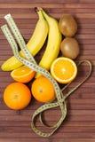 新鲜水果香蕉,猕猴桃,在一厘米包裹的桔子,隔绝在木背景 健康的食物 健身刺激 免版税库存图片