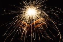 新年党闪烁发光物在黑背景的女性手上 免版税库存图片