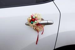 新年在一辆白色汽车的门的婚礼装饰 图库摄影