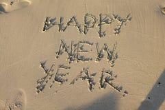 新年好消息在沙子海滩的手文字 库存图片