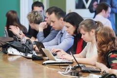 新闻工作者看看在扩大会议的膝上型计算机 库存图片