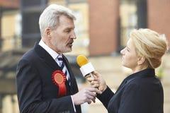 新闻工作者被采访的政客在竞选时 免版税库存照片