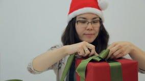 新年帽子的亚裔深色的妇女在演播室包裹当前箱子 股票录像